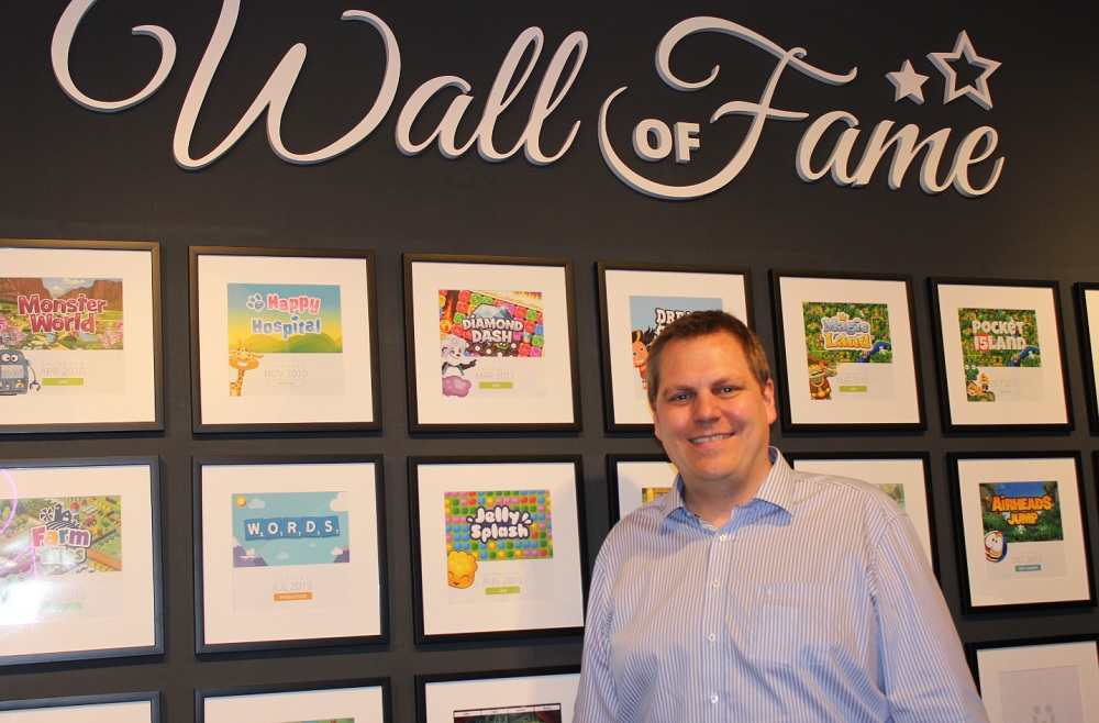 "Jens Begemann, the CEO of Wooga, at the ""Wall of Fame,"" where even canceled games are honored."
