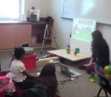 Kids using a Kinect-powered learning game about elementary physics.
