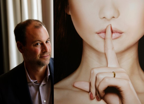 Ashley Madison founder Noel Biderman poses with a poster during an interview at a hotel in Hong Kong August 28, 2013.