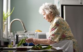 Elderly woman in kitchen properly cleaning fresh uncooked produc