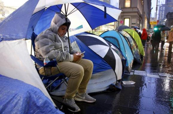 Marcus Barsum waits outside the Apple store in central Sydney Thursday. Reuters/David Gray