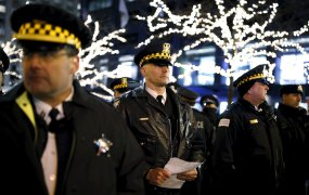 Police officers watch protesters during a demonstration in reaction to the fatal shooting of Laquan McDonald in Chicago, Illinois, November 27, 2015.