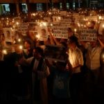 Những người tham dự dơ ảnh của blogger bất đồng chính kiến Nguyễn Hữu Vinh và nhà hoạt động bảo vệ đất Cấn Thị Thêu trong một buổi cầu nguyện kêu gọi công lý cho họ tại nhà thờ Thái Hà, Hà Nội (ngày 18 tháng 9 năm 2016).