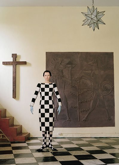 This image is all about the occult concept of duality - which is represented by the checkerboard pattern of Masonic ceremonial floors. The pattern is found on the floor in this picture and Tilda is literally completely draped in it. The setting also includes religious artifacts - symbols giving the Tilda's wardrobe an ethereal meaning.