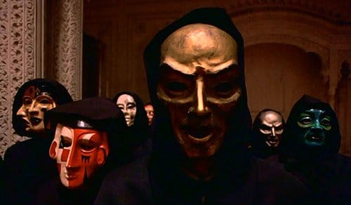 "Silently looking right at the camera (and at the movie viewers), the creepy masks are silent yet disturbing reminders showing the ""true faces"" of the elite. Note that the multi-faced mask on the left is similar to the one worn at the Rothschild party above."