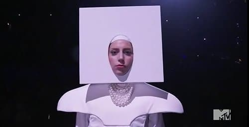"Gaga began her performance with her head stuck in a white square - maybe a way of saying that she's a ""blank canvas"" that is ready to be painted in any way possible to get applause."