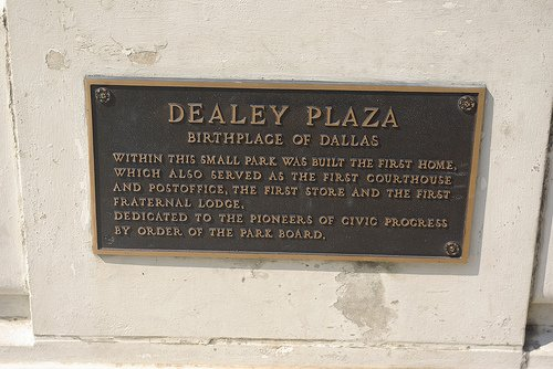 """A placa na parte inferior menciona que Dealey Plaza é o local de Dallas 'primeiro """"Fraternal Lodge"""", que é uma Loja Maçônica."""