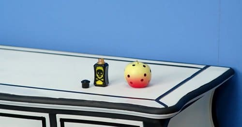 In this scene, we see a vial of poison turning a red apple yellow with black dots. This pattern will represent death throughout the rest of the video.
