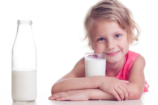 Girl drinks milk from glass on white background