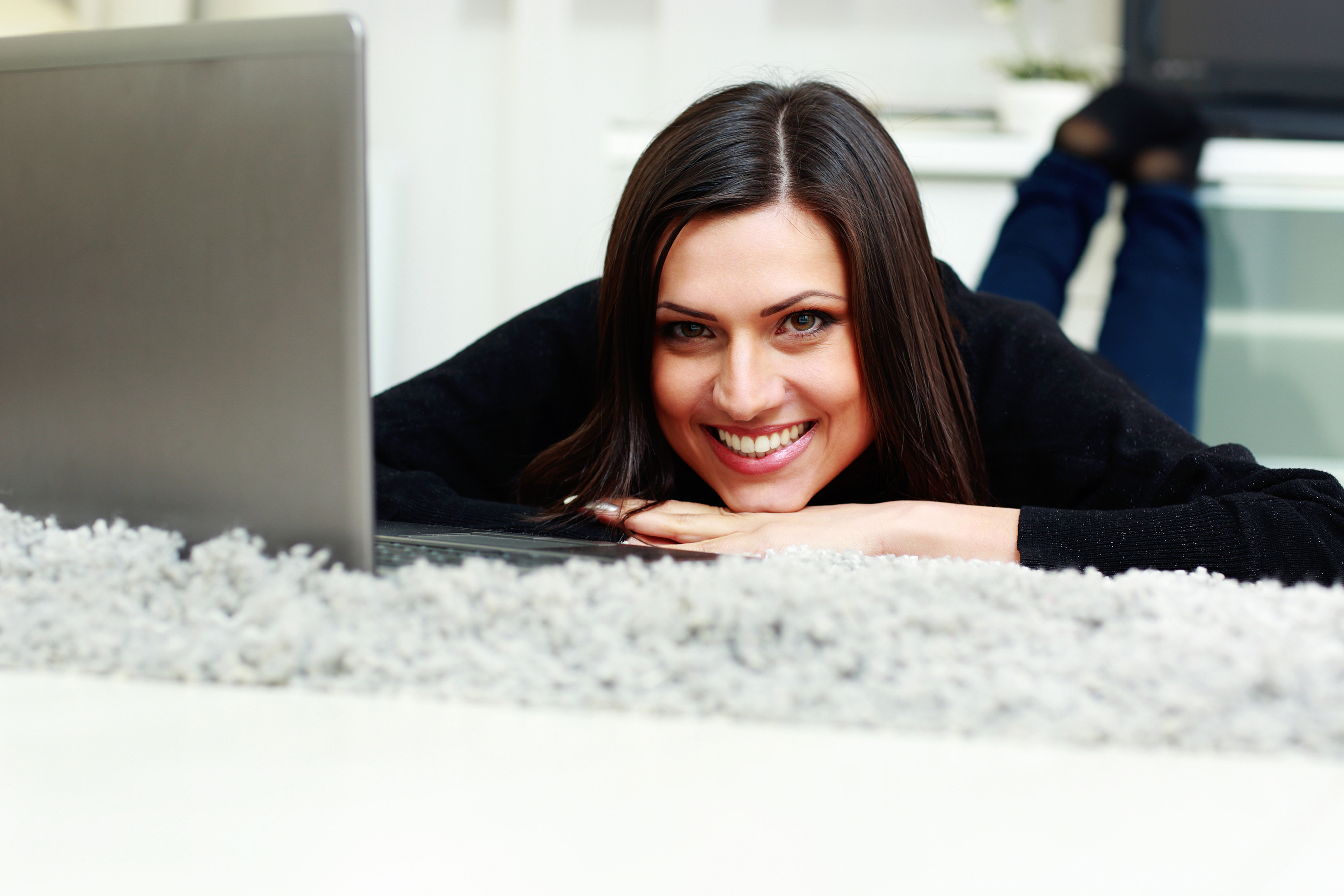 Portrait of a young happy smiling woman lying with laptop at home