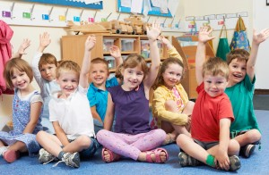 a group of young schoolchildren in class putting their hands up to answer questions