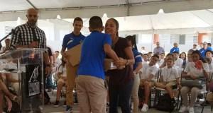 Un estudiante recibe su computadora de manos de la alcaldesa de Salinas, Karilyn Bonilla.