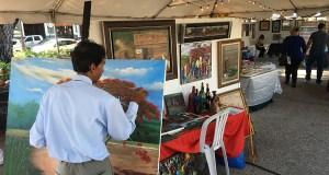 Un artista pinta en vivo durante la Feria de Artesanías y Muestra de Arte. (Voces del Sur)