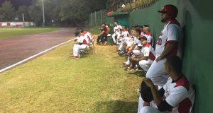 Jugadores de los Petateros de Sabana Grande observan la acción en el terreno de juego.