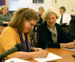 Sen. Diane Snelling signs the budget conference committee report as Sen. Jane Kitchel looks on. Photo by Anne Galloway