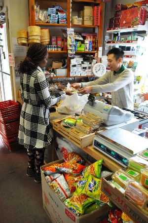 Loc Tran (Anthony) serves a customer at Thai Phat, the market on North Street in Burlington that his family bought five years ago. Photo by Dirk Van Susteren
