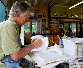 Richard Erdmann creates his unusual stone and bronze sculptures by first modeling them in plaster. Here, he works at his modeling table in his Williston studio.Photo by Andrew Nemethy/VTDigger