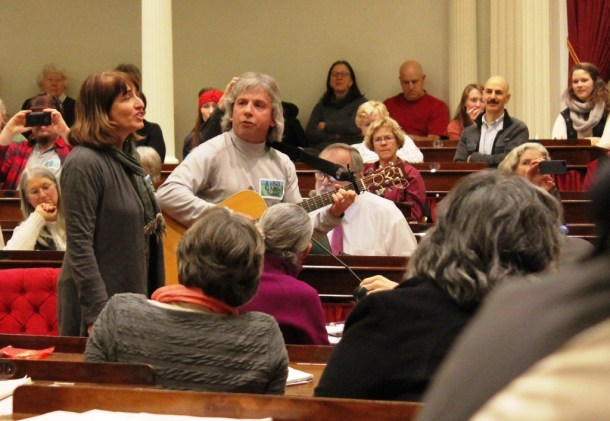 Janice Russotti and Shane Bowley, both of South Burlington, deliver their testimony on a GMO labeling bill in song. Photo by Andrea Suozzo/for VTDigger