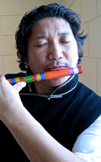 Mingmar Tsering, president of the Tibetan Association of Vermont, plays a traditional flute at a recent celebration of Tibetan culture at the Fleming Museum. Photo by Tom Slayton