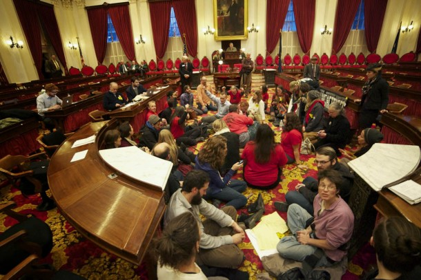 Protesters, some of whom are with the Vermont Workers Center, stage a sit-in on the floor of the Vermont House chamber. Photo by John Herrick/VTDigger