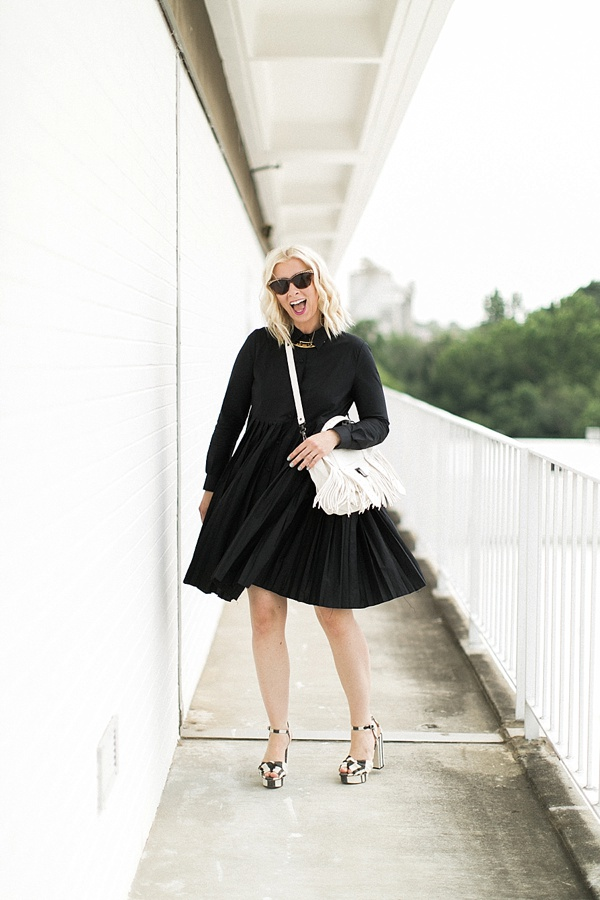 Black dress with pleats and white fringe bag