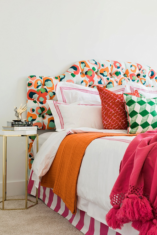 Colorful cheetah print headboard with pink throws