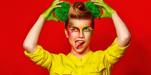 Cheerful girl with make-up broccoli demonstrates positive emotions. Concept of healthy food and organic products.