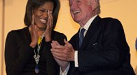 Michelle Obama leads the applause for Sen. Ted Kennedy.