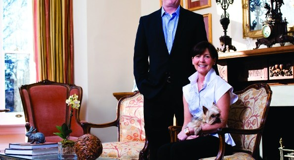 """In the formal front parlor, P.L. """"Skip"""" Singleton Jr., Debbie Singleton and their yorkie Little General MacArthur sit amid collected treasures that include the French clock and candelabras on the mantelpiece purchased at Onslow Square Antiques in Kensington, Md. The chandelier is a French spider arm and the coffee table is a repurposed outdoor bench."""