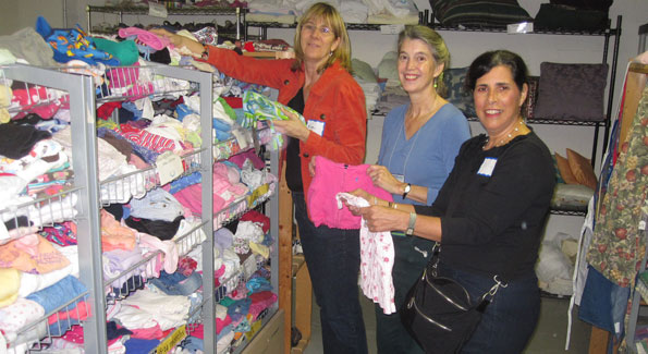 Kim Schifrin, Barbara de Boinville and Joan Levy sort baby clothes for A Wider Circle.