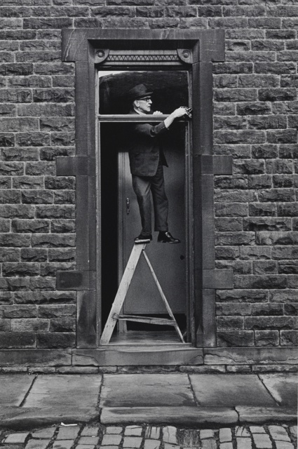 Hebden Bridge,Tom Greenwood cleaning. 1976. by Martin Parr.jpg