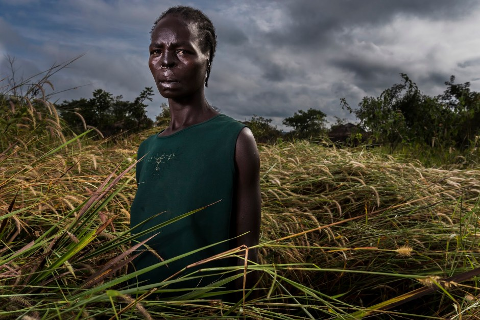 GULU, UGANDA, 21 November 2014: Margret Acino, 32, is one of hundreds of thousands of victims of the L.R.A; a rebel group that now relies heavily on ivory to fund their terror campaign. She was attacked by members of the Lord's Resistance Army when she was 23 and 9 months pregnant. Her lips, ears and nose were cut off and her breasts were hacked off by the rebels. Margret and a small group of villagers had gone to the fields for crops when they found themselves surrounded. They were taken quickly to an area outside of Gulu where the men accused them of informing on the LRA to the Ugandan Army. Two men and a child were then immediately killed with the hoes they had been carrying for farming. The commander of the rebels accused them again, confronting Margaret and accusing her of being the wife of a soldier. Her husband was in fact a simple farmer. The LRA commander then killed another women in front of her. He said this must be the truth or how could she be so confident in talking with them. He then said he would teach her not to inform ever again. He ordered his men, mostly young teenagers, to produce a razor blade. They hesitated and the commander then threatened his own men, one of them then produced a razor blade and they were ordered to cut off Margret's lips, ears and nose, a practice that was an LRA trademark at the time. When the men were finished, Margret was released and told to run. She passed out from loss of blood shortly thereafter and when she revived she found a man with a bicycle who took her to an IDP. She was in surgery for 2 days, her baby was born via an emergency caesarian and Margret then lapsed into a coma for 5 days. She has had 7 surgeries since to try to repair her ravaged face. The LRA commander who ordered this brutality subsequently defected and was given amnesty. Margaret saw him at a World Vision camp and became hysterical, telling people he was the one behind her tragedy. He was moved from the camp but not prosecuted. Margret has subs