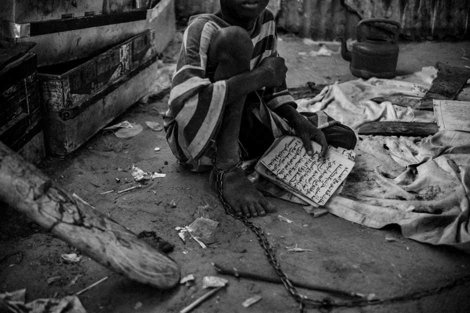 """A young talibe bound by chains in an isolation area of a daara in the city of Touba, May 27, 2015. In this daara the youngest talibes are shackled by their ankles to stop them from trying to run away. The chains length only allows them to use an improvised bathroom in a separate area of the daara. These children can stay like that for days, weeks, even months until they gain the marabout's trust. Their guardian explains """" When I release them, I give them the freedom to beg like the rest of the Talibes""""."""