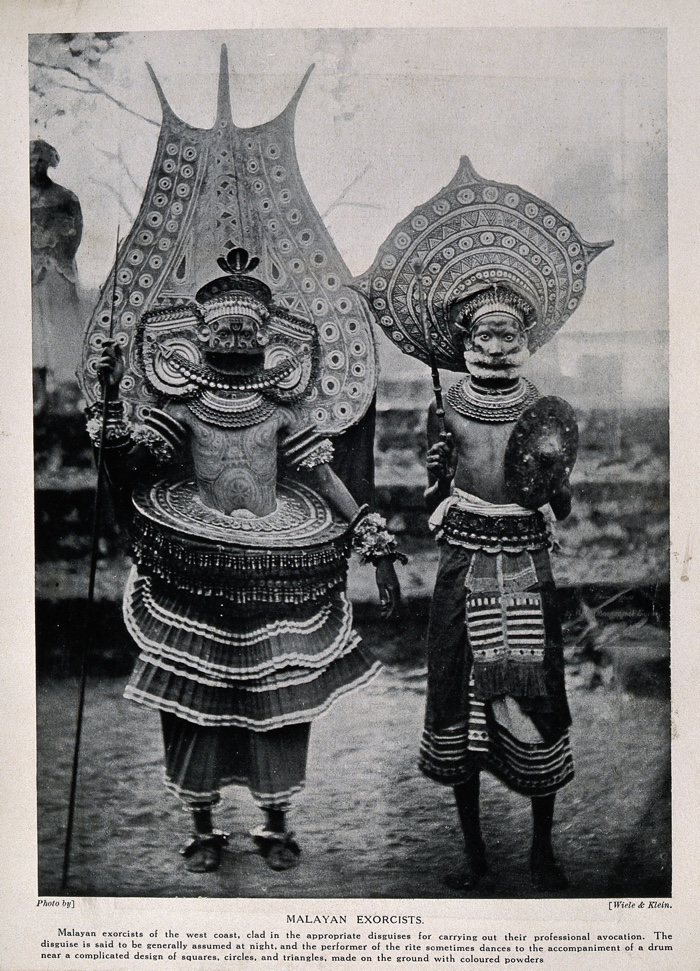 V0015993 Two Malayan exorcists dressed in elaborate ritual costume. H Credit: Wellcome Library, London. Wellcome Images images@wellcome.ac.uk http://wellcomeimages.org Two Malayan exorcists dressed in elaborate ritual costume. Halftone after a photograph by Wiele & Klein. By: Wiele & Klein.Published:  -  Copyrighted work available under Creative Commons Attribution only licence CC BY 4.0 http://creativecommons.org/licenses/by/4.0/