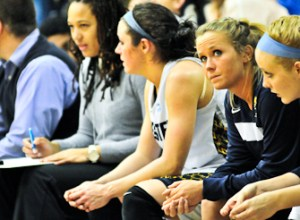 From right to left: Webster University freshman Kylie Fenemor, sophomore Hillary Trimble and junior Maggie Zehner watch from the bench during their team's 81-65 loss to Eureka College on Feb. 4 at Grant Gymnasium. PHOTO BY SEAN SANDEFUR.