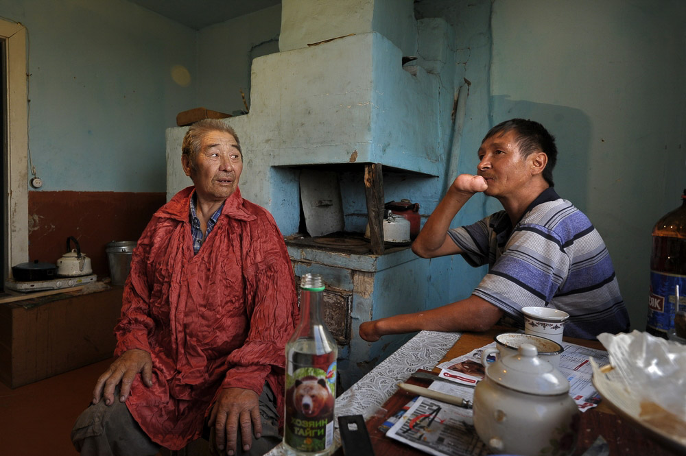 Son without hands sitting with his old father in Abakan Khakasia Russia