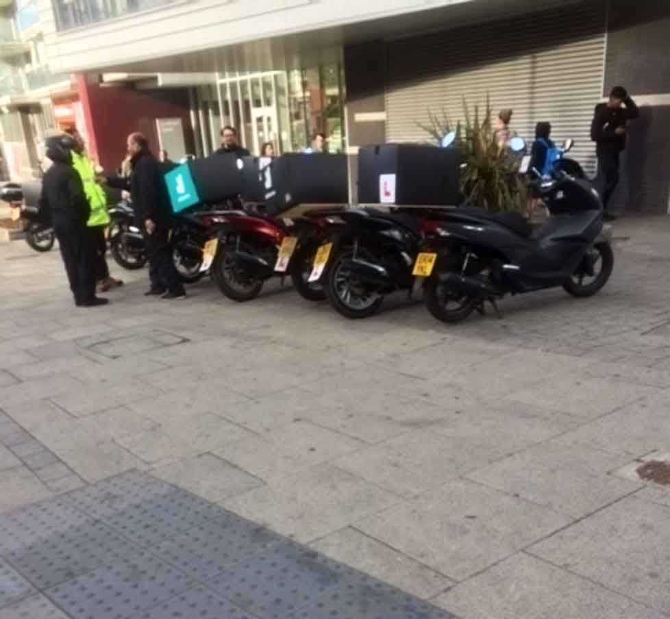 deliveroo scooters parked outside tesco