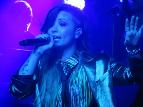 Demi wears metallic blazer and tie during G-A-Y performance