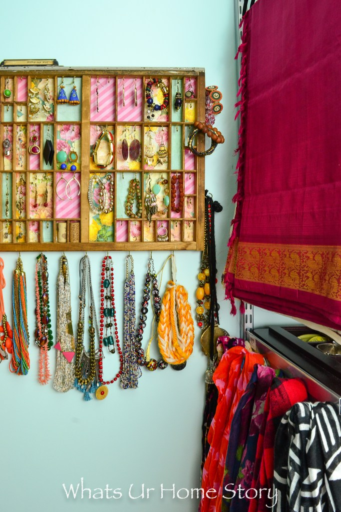 small-walk-in-closet-organization-letter-press-tray-jewelry-organizer-and-scarves-hung-from-hooks-on-the-side-of-elfa-shelves