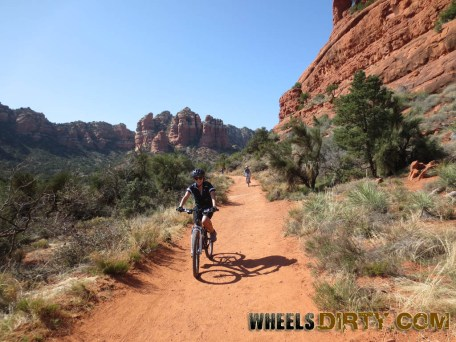 Anneka is all smiles as she rides down this smooth fire road beside the enormous Bell Rock mountain.