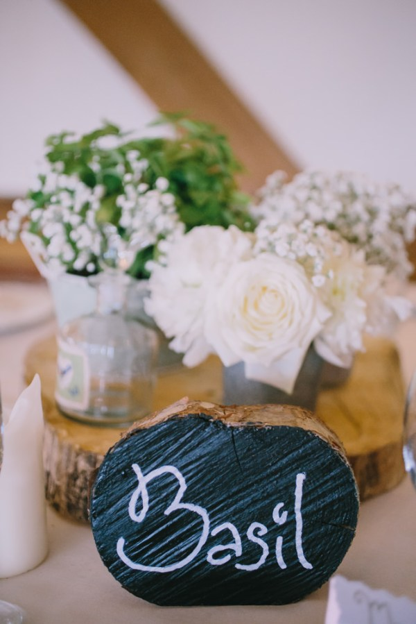 Stylish White DIY Floral Filled Barn Wedding Log Chalkboard Blackboard Table Names  http://www.chrisbarberphotography.co.uk/