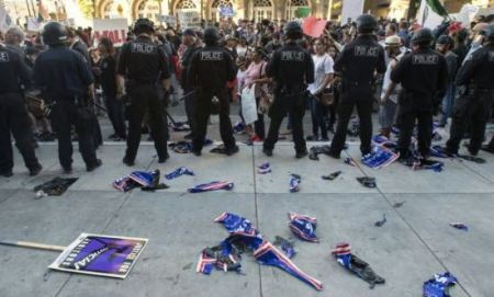 Torn campaign signs litter the ground behind a police skirmish line on June 2 during a protest near where Donald Trump held a rally in San Jose, Calif. (JOSH EDELSON/AFP/Getty Images)