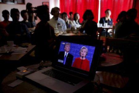 People watch live broadcast of the first U.S. presidential debate between Republican U.S. presidential nominee Donald Trump and Democratic U.S. presidential nominee Hillary Clinton at a cafe in Beijing, China on September 27, 2016. REUTERS/Damir Sagolj/File Photo