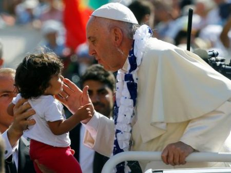 Pope Francis interacts with a child as he arrives for the audience for workers and volunteers of mercy at the Vatican, on Sept. 3, 2016. Photo courtesy of Reuters/Stefano Rellandini