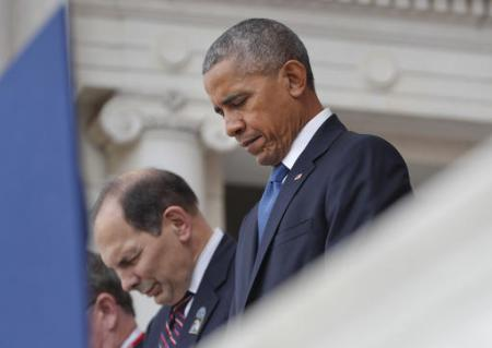 President Barack Obama and Veterans Affairs Secretary Robert McDonald bow their heads during opening prayers before the president spoke in the Memorial Amphitheater at Arlington National Cemetery in Arlington, Va., Friday, Nov. 11, 2016, during a Veterans Day ceremony. (AP Photo/Pablo Martinez Monsivais)