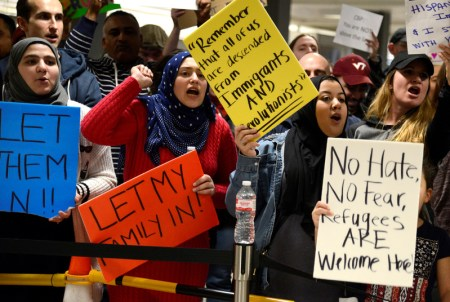 Dozens of pro-immigration demonstrators cheer and hold signs as international passengers arrive at Dulles International Airport, to protest President Donald Trump's executive order barring visitors, refugees and immigrants from certain countries to the United States, in Chantilly, Virginia, in suburban Washington, U.S., January 29, 2017.  REUTERS/Mike Theiler