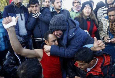 (PHOTO: REUTERS/YANNIS BEHRAKIS) A stranded Iranian woman cries as she embraces a colleague who just had his mouth sewed shut during a protest at the Greek-Macedonian border near the Greek village of Idomeni November 26, 2015. Countries along the Balkan route taken by hundreds of thousands of migrants seeking refuge in western Europe last week began filtering the flow, granting passage only to those fleeing conflict in Syria, Iraq and Afghanistan.