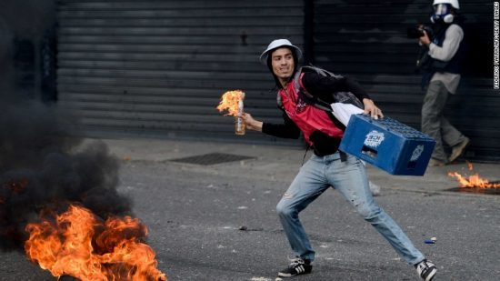 A protester aims a Molotov cocktail at police on April 19. Venezuela's political crisis has intensified since the government notified main opposition leader Henrique Capriles on April 7 that he had been banned from political activity for 15 years. This came during protests denouncing the Supreme Court rulings issued on March 29, which curbed the powers of the opposition-controlled legislature.