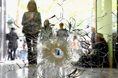 People look at a bullet hole in a window near to the Marks and Spencer on the Champs Elysees in Paris following the shooting of a police officer, 21 April (GETTY IMAGES)