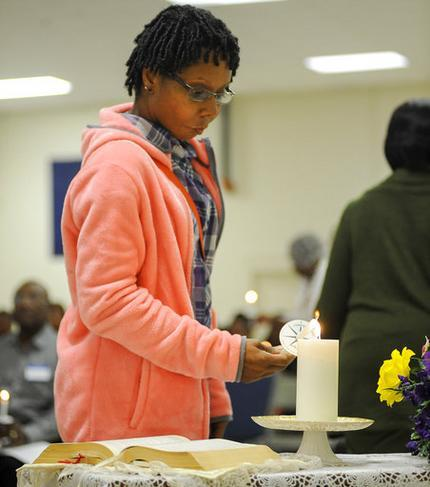 Tabitha Julkes lights a candle during a ceremony near Tuskegee, Ala., on Monday, April 3, 2017, to commemorate the roughly 600 men who were subjects in the Tuskegee syphilis study. Julkes' great-grandfather Albert Julkes was a test subject, and she is among the descendants of men who are now stepping forward publicly to tell their stories. (AP Photo/Jay Reeves)